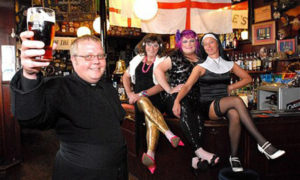 FOR SUNDAY   Dated: 13/03/2011 The Reverend Martin Wray, of St Lawrence the Martyr Church in South Shields, South Tyneside, who has retired from the Church, after recently causing alarm amongst parishoners by being pictured wearing gold leggings and shocking pink high heels for a controversial 'vicars and tarts' fundraising party. L-R: Party organiser Dave Wood, Rev Martin Wray (in gold leggings), Lee Wray and Kerry Lee at The Steamboat pub in South Shields. See story North News